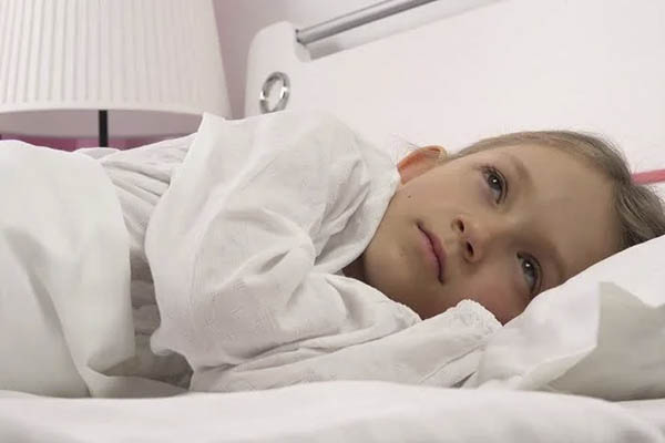 child in bed awake