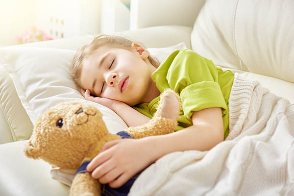 child sleeping with doll